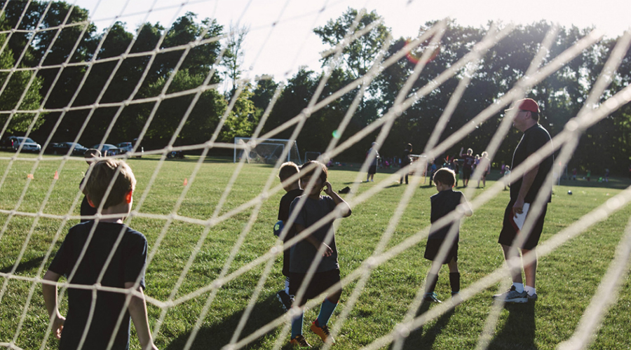 residential kids playing soccer with net 900x500