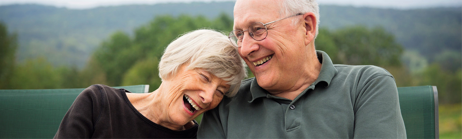 Retired couple sitting outside and laughing.