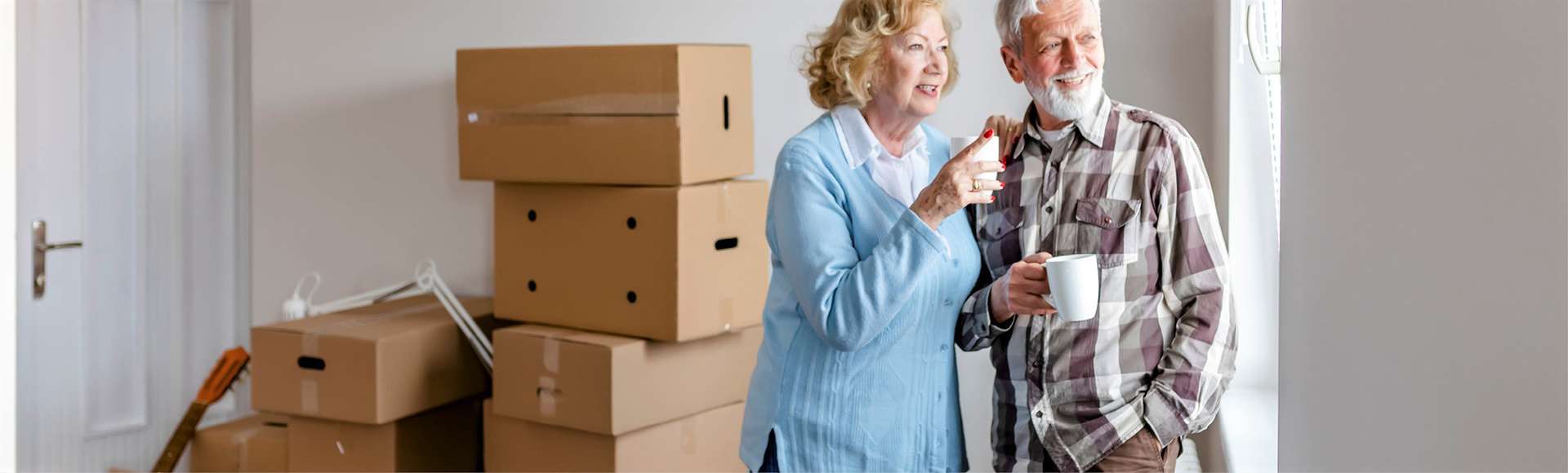 Elderly couple stand in a room surrounded by boxes.