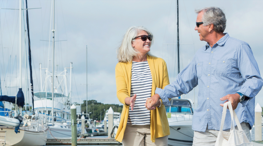 Two retirees walking along a Marina