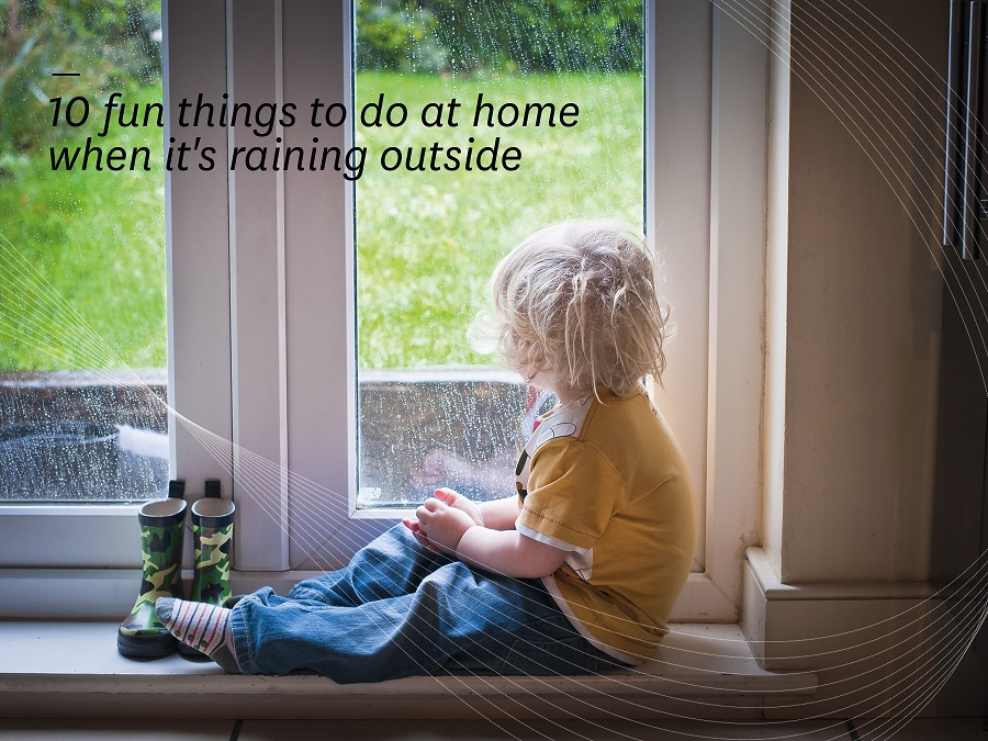 Child sitting on a window ledge looking outside as it rains