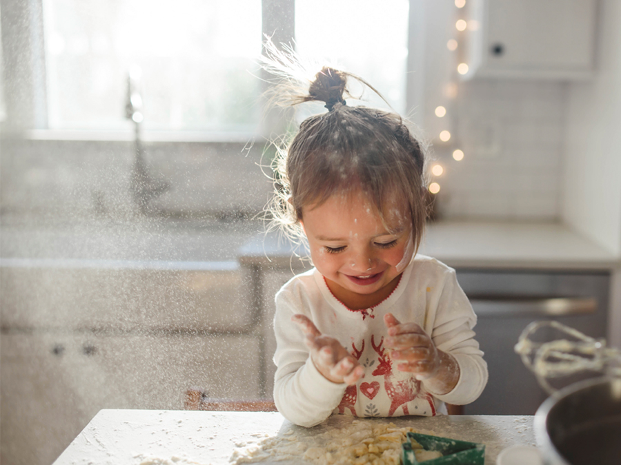 Little girl playing with flour